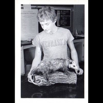 A young Gray Staab proudly admiring his taxidermied opossum.
