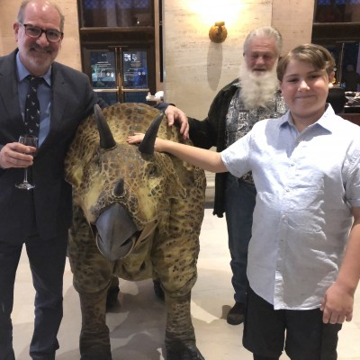 Luis and his son Luca hanging out with a Triceratops puppet at a party at the Natural History Museum of LA County.